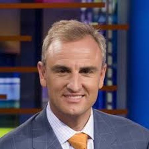 Trey Wingo in a blue suit poses for a picture.