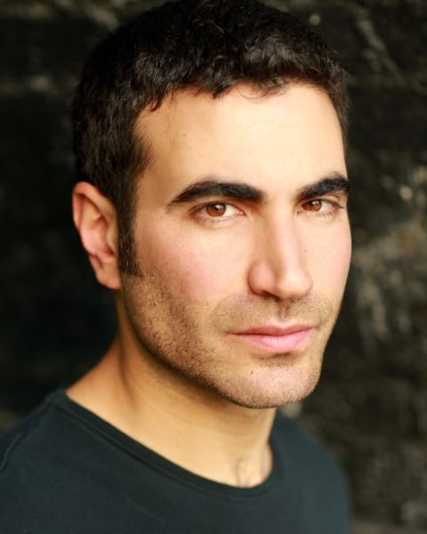Brett Goldstein in a black t-shirt poses for a picture.