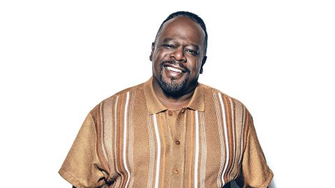 Cedric the Entertainer in a brown t-shirt poses for a picture.