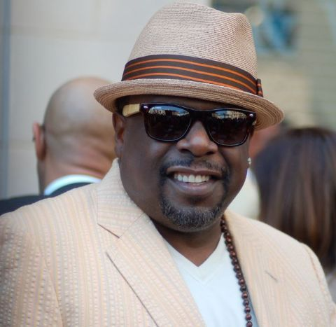 Cedric the Entertainer in a brown coat poses for a picture.