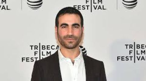 Brett Goldstein in a black suit poses for a picture.