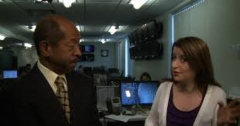 Kwame Holman in a black suit caught in the camera while talking to a colleague.