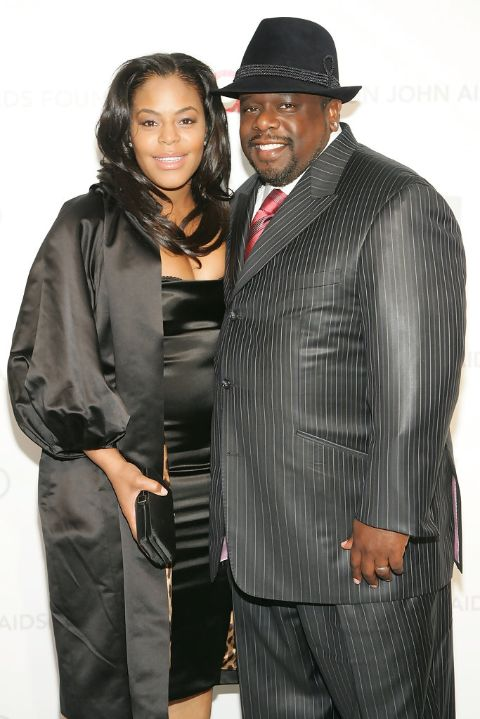 Cedric the Entertainer in a black suit poses a picture with his wife Lorna Wells.