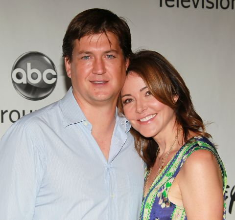 Bill Lawrence in a white shirt poses a picture with wife Christa Miller