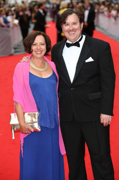 Mary Roscoe in a blue dress poses a picture with her husband Jeremy Swift.