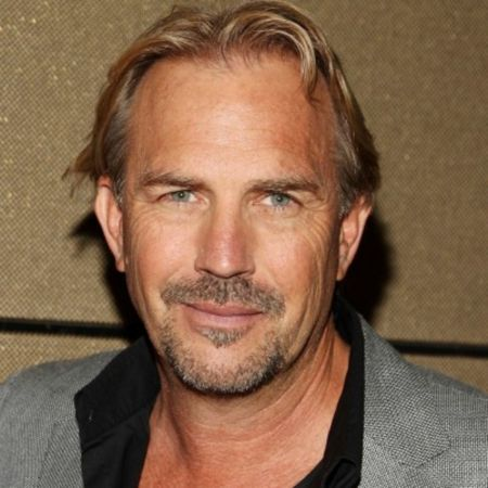 Kevin Costner in a grey suit poses a picture.