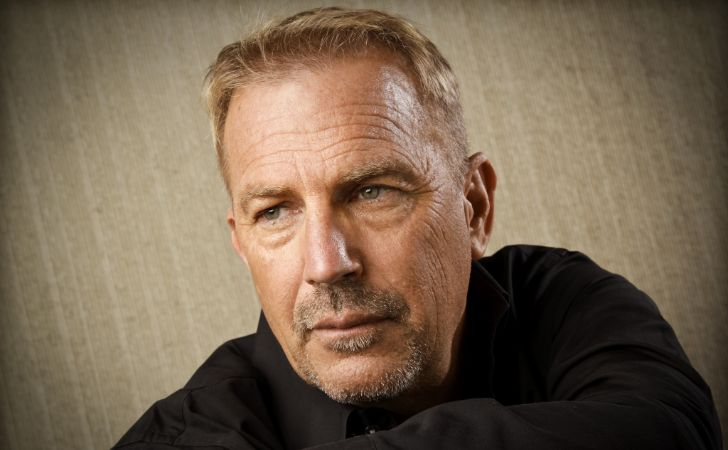 Kevin Costner in a black sweater poses for a picture.