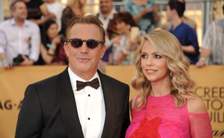 Christine Baumgartner in a pink dress with husband Kevin Costner.