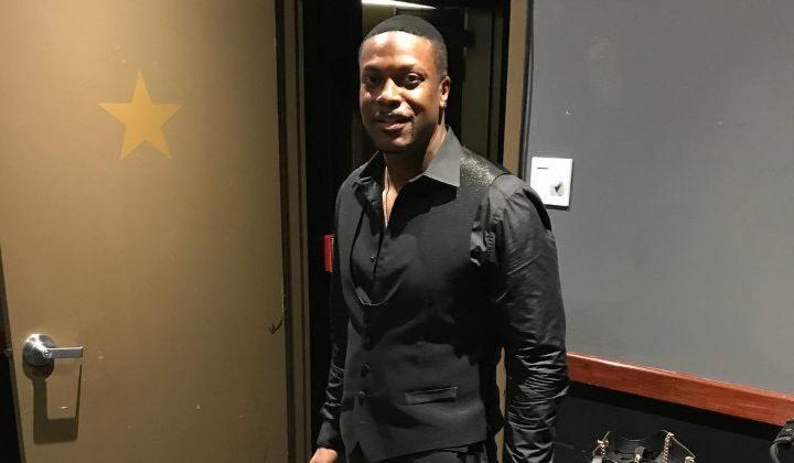 Chris Tucker in black shirt and waist coat