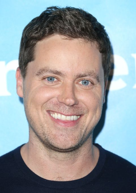 Greg Poehler in a black t-shirt poses a picture.