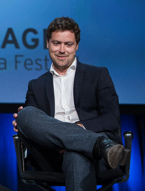 Greg Poehler in a black suit poses a picture.