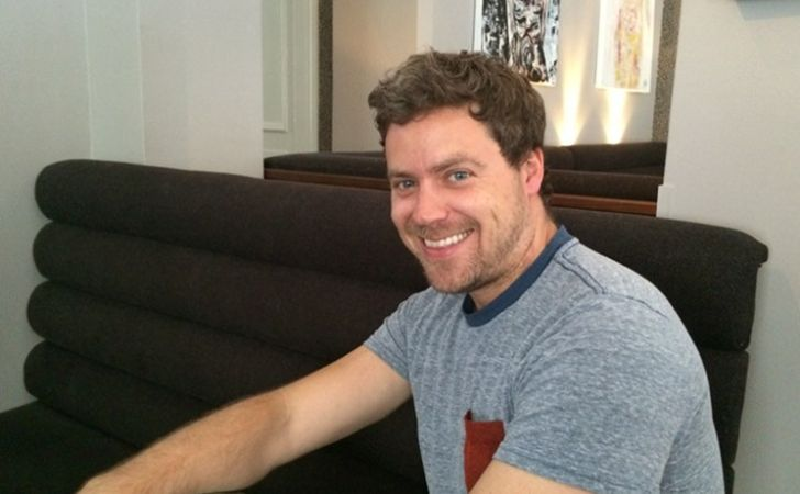 Greg Poehler poses a picture in a grey t-shirt.