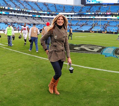 Laura Okmin poses for a picture in a football stadium.