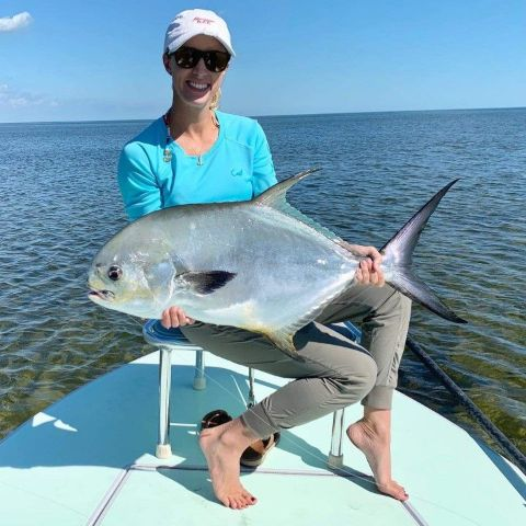 Vicky Stark holding a fish in ocean.
