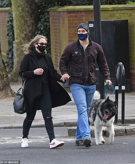 Henry Cavill wore and his girlfriend wore a mask throughout the walk.