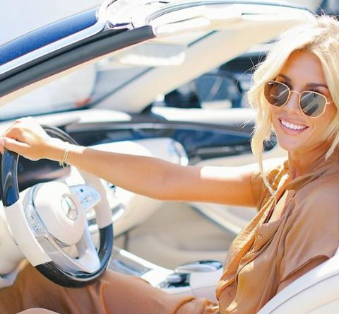 Charissa Thompson is driving a car. she is clicking photo with her car.