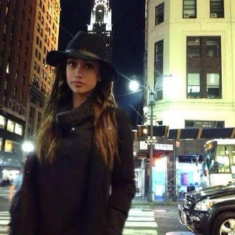 Ria enjoying her night time in the city. She is wearing a black sweater.